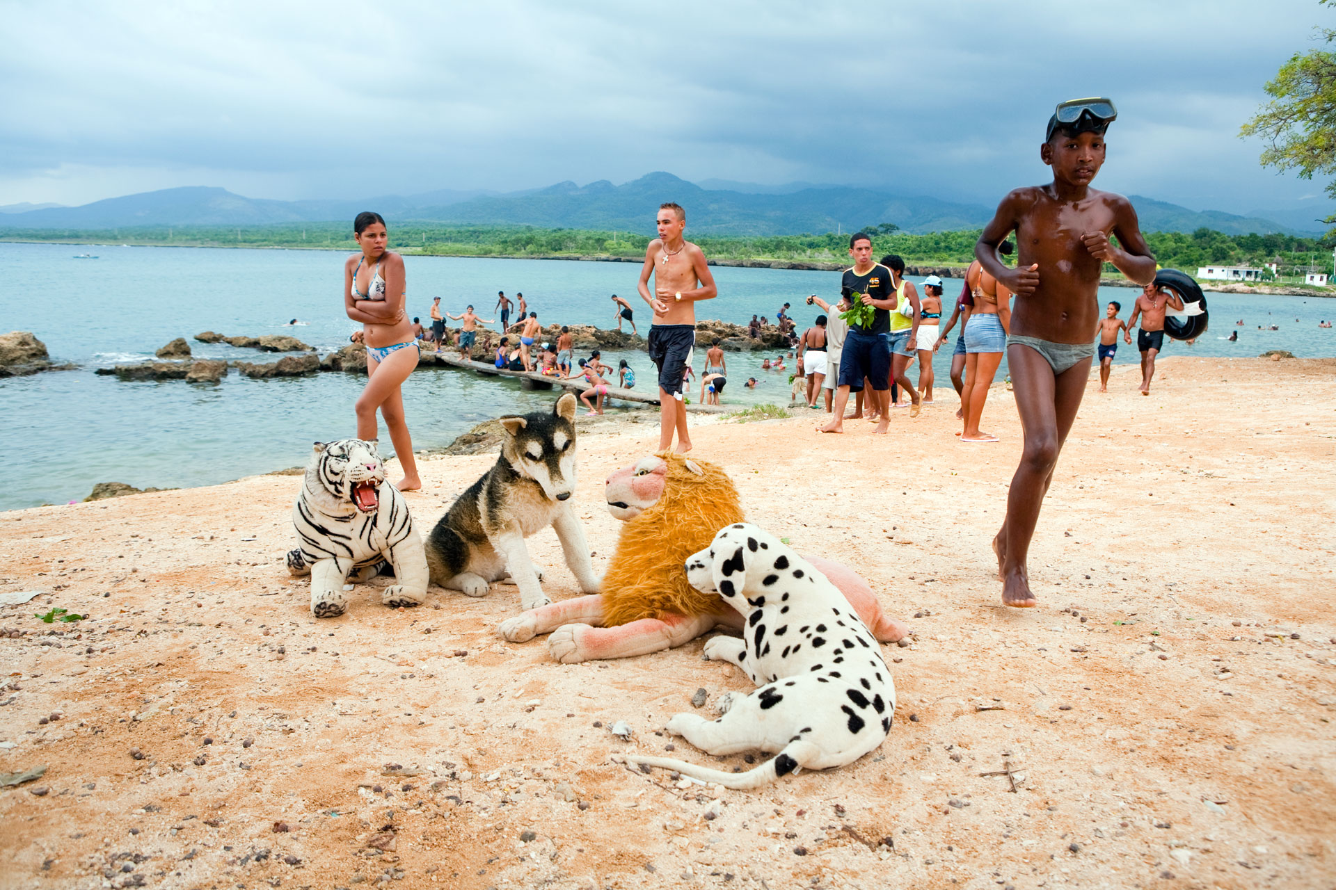 Jason Florio photography - color image of children on a beach in Cuba, with large stuffed animals, against a blue stormy sky