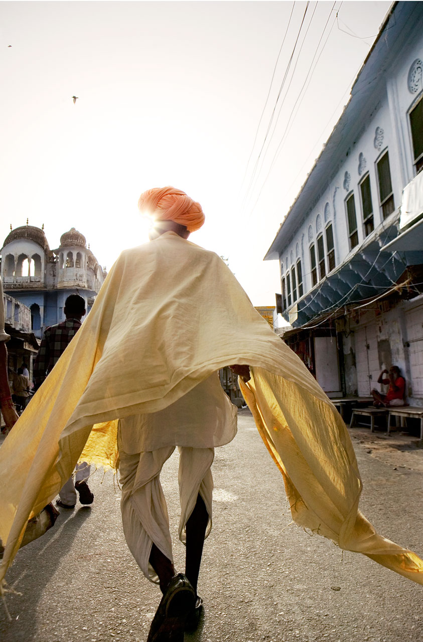 Jason Florio photography - color image of an Indian man walking away from the camera, in yellow robes, Pushkar, India
