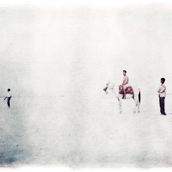 ©Oskar Landi #3- ALSO IN INDIA. Color. Polaroid. 3 Indian men, one on a horse, against a stark white background
