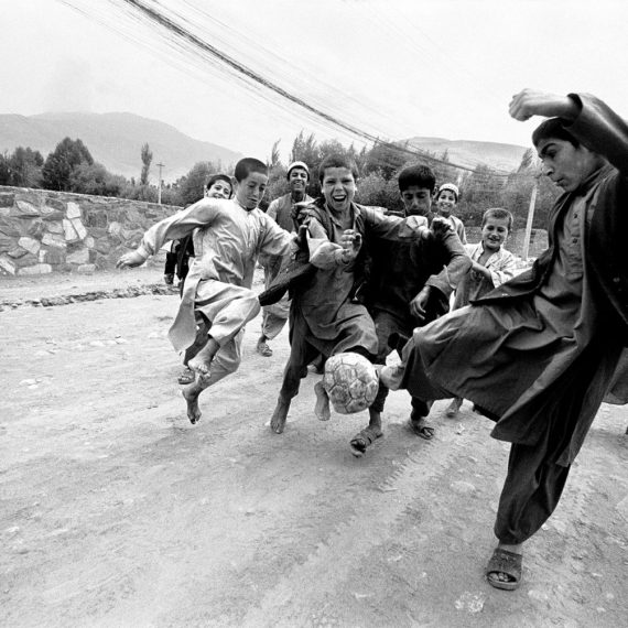 @Jason Florio - Soccer Boys Afghanistan. BW group of young boys kick around a deflated football on the road