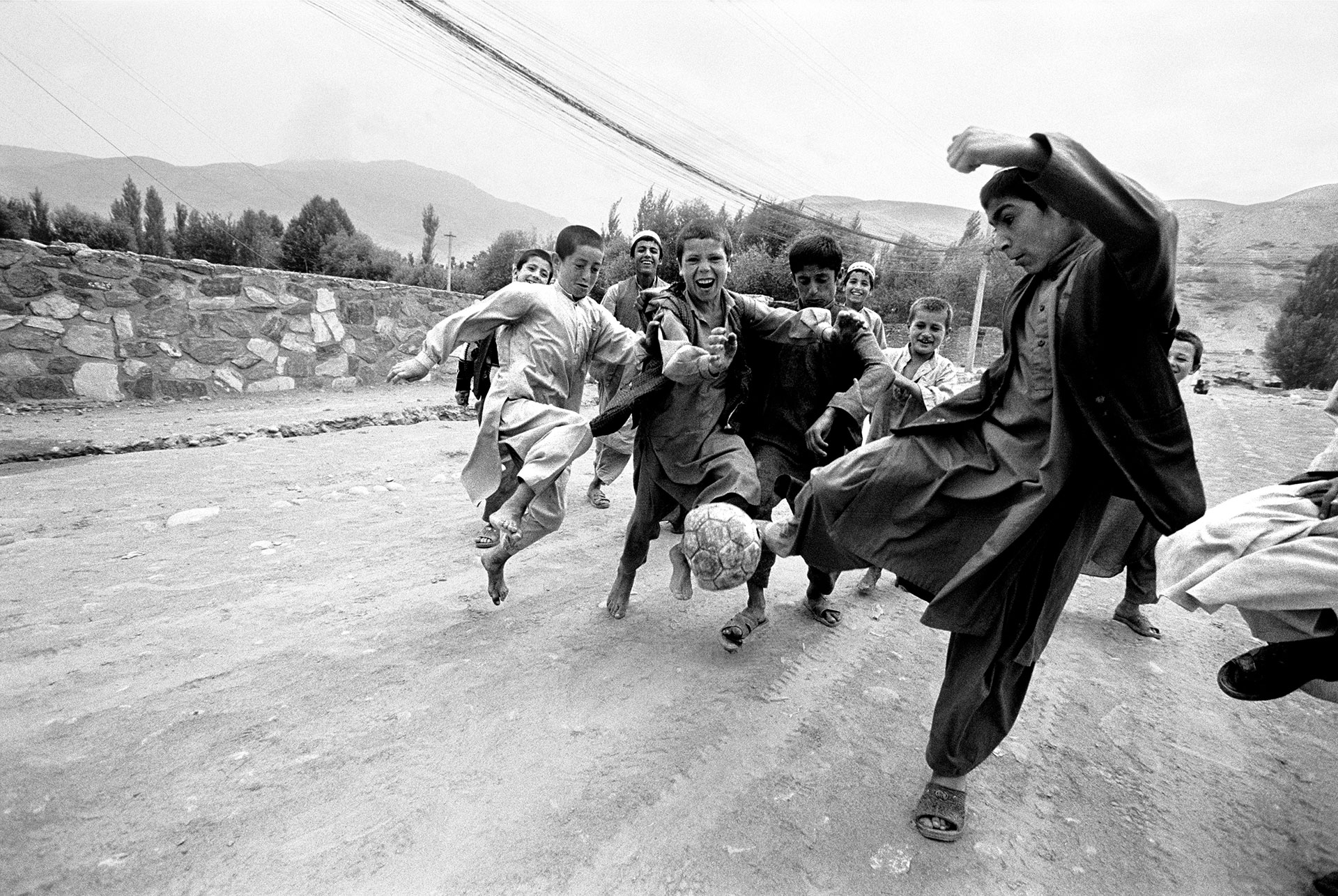 Jason Florio photography - black and white image of a group of you boys kicking around a deflated football (Soccer ball), in a rural street, Afghanistan