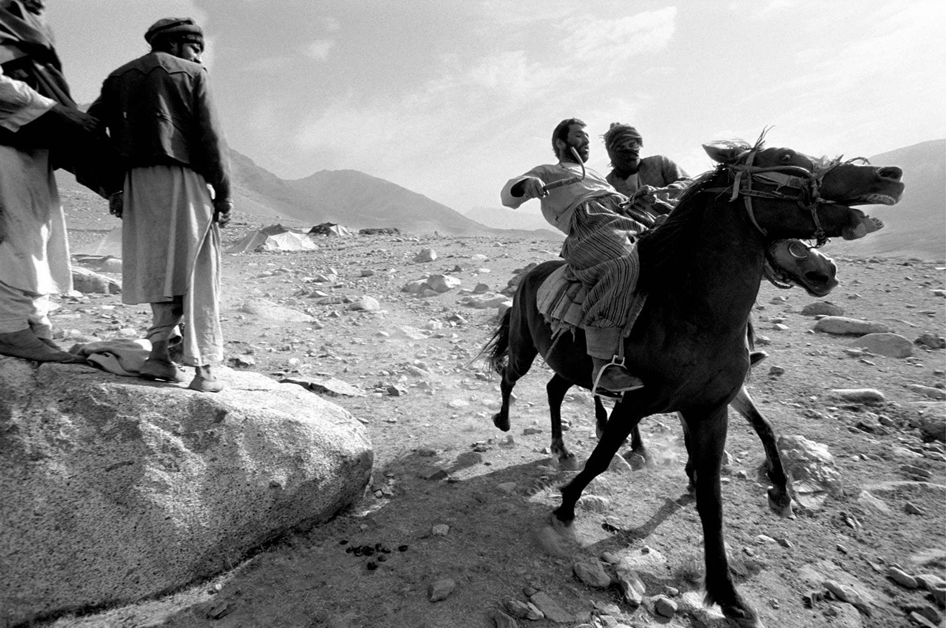 Jason Florio photography - black and white image of two Nomad men racing their Horses, as two other men watch on, in the mountains - rural Afghanistan