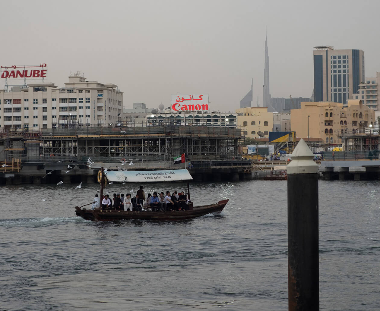 A traditional abra ferry crossing the Dubai Creek with the Burj Khalifa in the distance