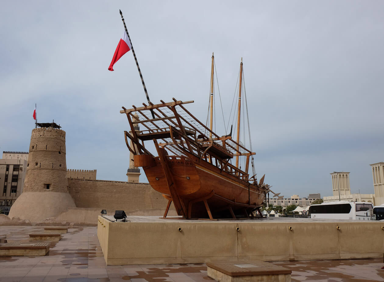 A huge dhow sailing ship in front of the Al Fahidi fort
