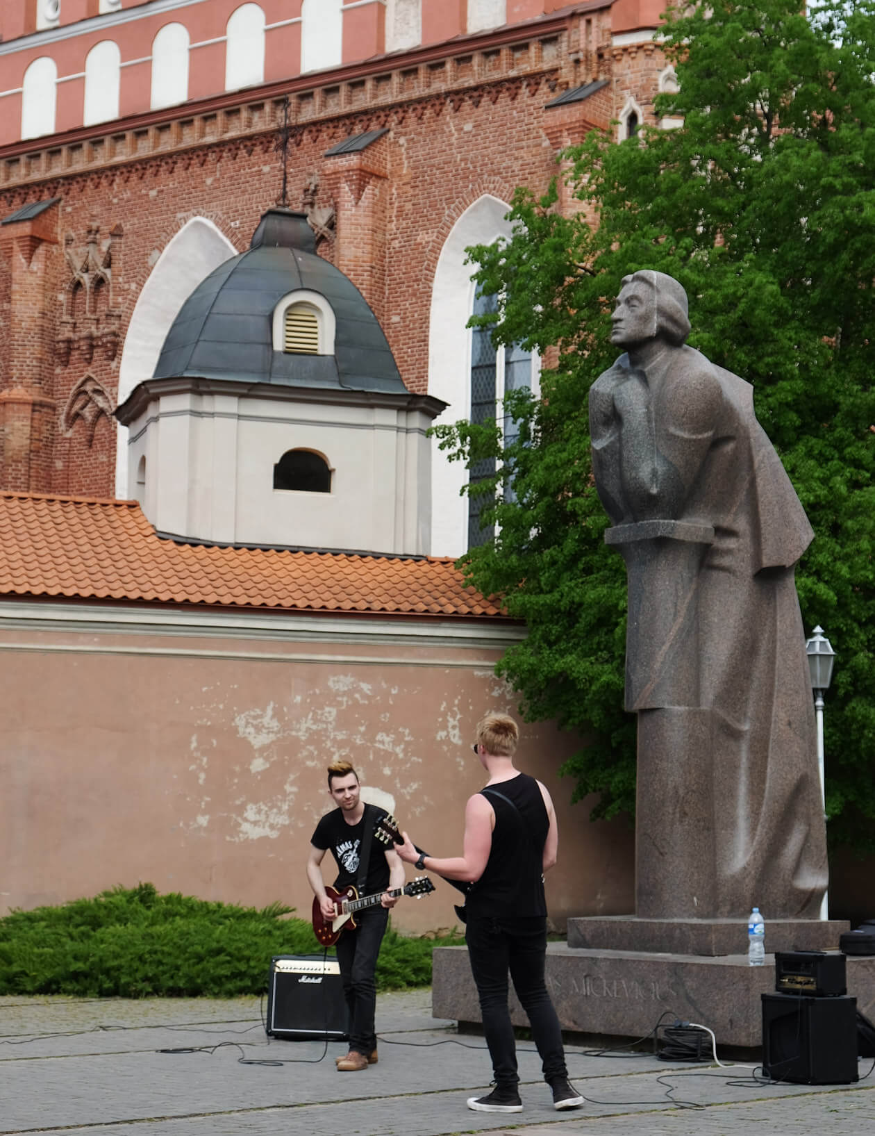 A duo rocking out in front of the statue of Adam Mickiewicz, Lithuania's national poet