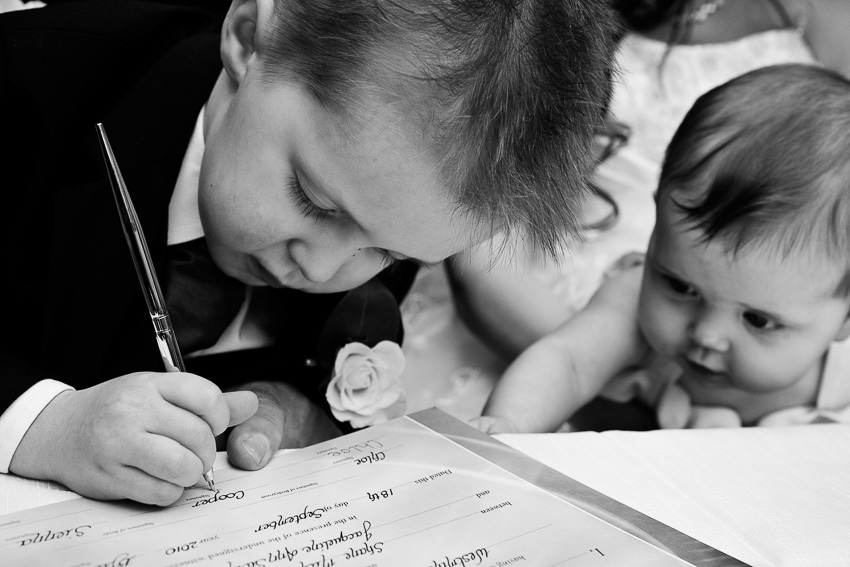 Kids at wedding signing a familly wedding certificate