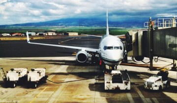 A photograph of an airplane parked on the tarmac at Kahului Airport, in Maui, Hawaii.