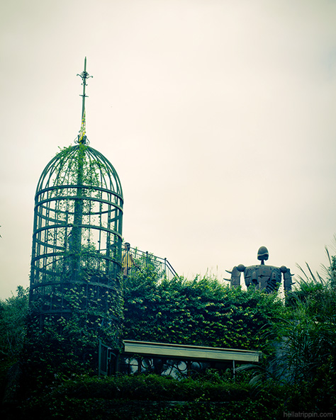The rooftop of the Ghibli Museum is accessed via a spiral staircase. A robot soldier from Laputa: Castle in the Sky stands guard silently.