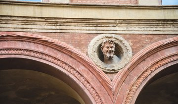 A sculpted head peers from out of an architectural detail of a portico in central Bologna, Italy.