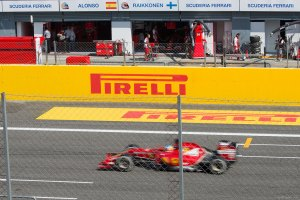 Fernando Alonso (#14) zooms down the start-finish straight past the paddock during Saturday's qualifying round.