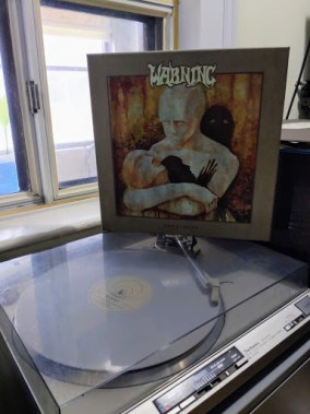 Record player and album cover for Warning - The Albums