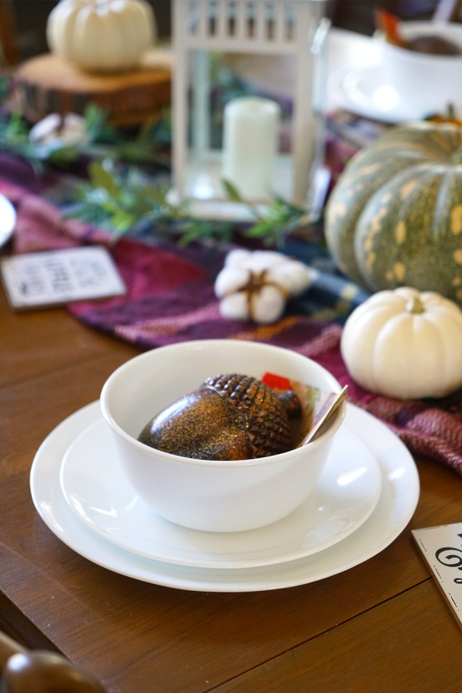 White Corelle dinnerware set with glittery acorn, wood table, and plaid blanket.