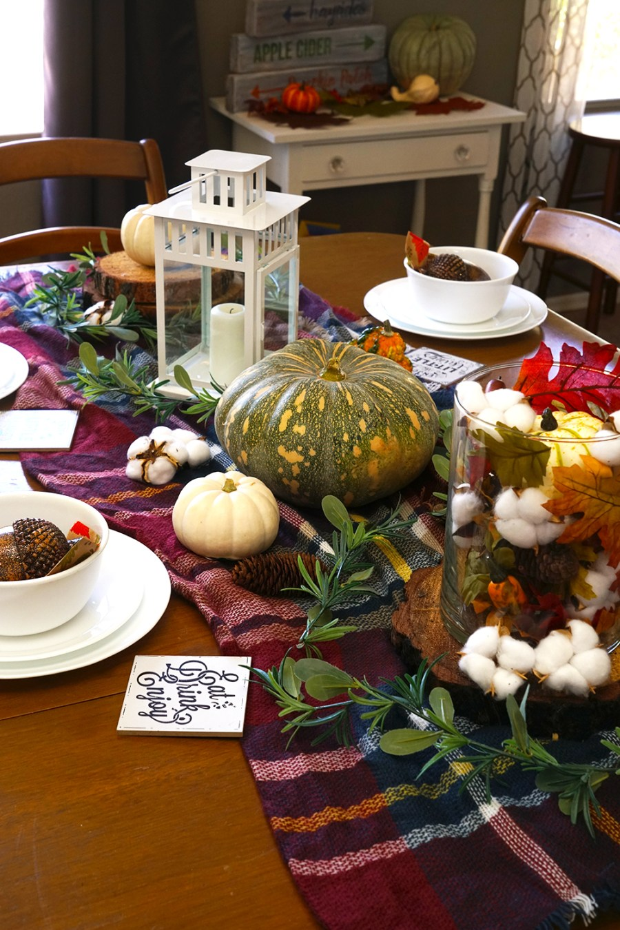 fall tablescape on a wood table with a plaid blanket