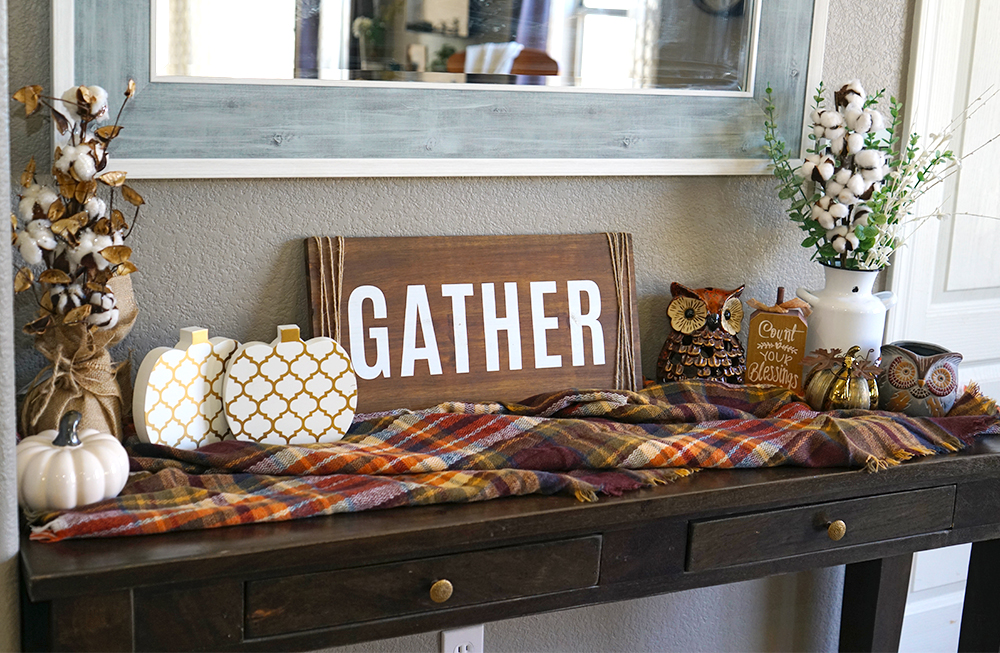 Wood table with a plaid fall blanket, cottom stems, and white pumpkins