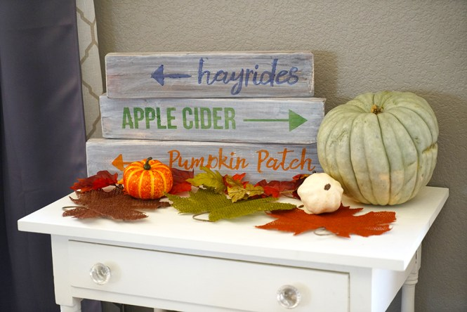 white table with wood signs and pumpkins