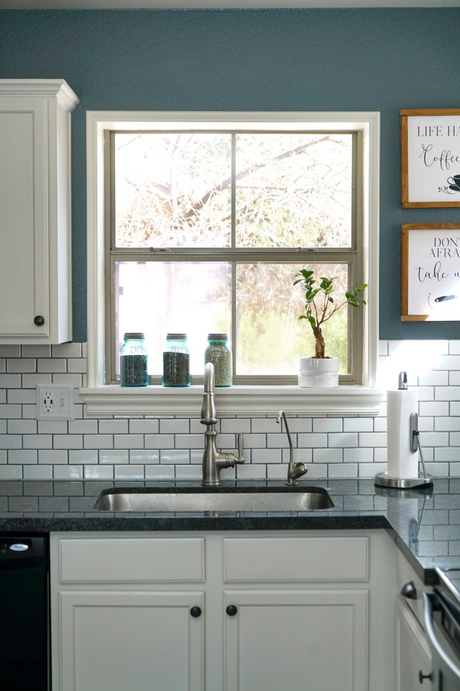 white cabinets with dark gray countertops, DIY framed windows and etsy decor