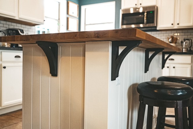 details of the kitchen island with the side paneling, butcher block countertop and dark gray corbels