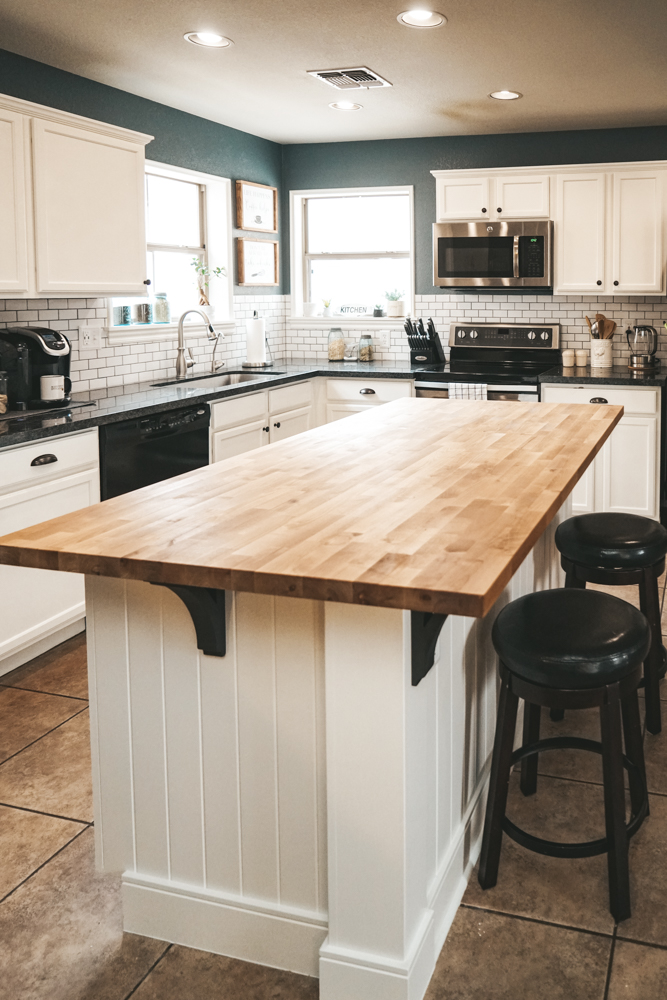butcher block countertop on a kitchen island with white cabinets and subway tile