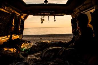 Blick aus einem Van auf das Meer bei Sonnenuntergang