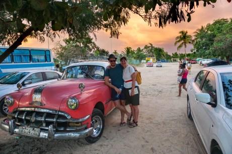 Rosa Taxi am Strand bei Sonnenuntergang in Kuba