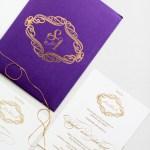 gold initials on purple invitation