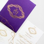 gold initials on purple invitation