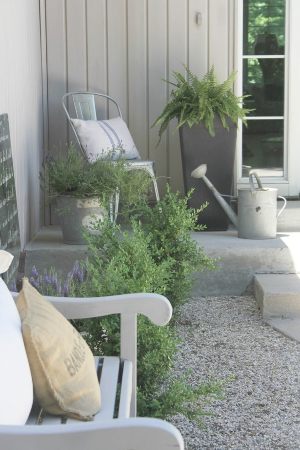 French farmhouse style courtyard with pea gravel, bench, boxwood, and galvanized farmhouse buckets - Hello Lovely Studio.
