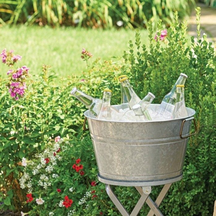 Galvanized round tub with ice and cold drinks ready for a party in summer. Come see my Farmhouse French Inspired Courtyard, Inexpensive Bistro Dining Sets & Garden Finds.