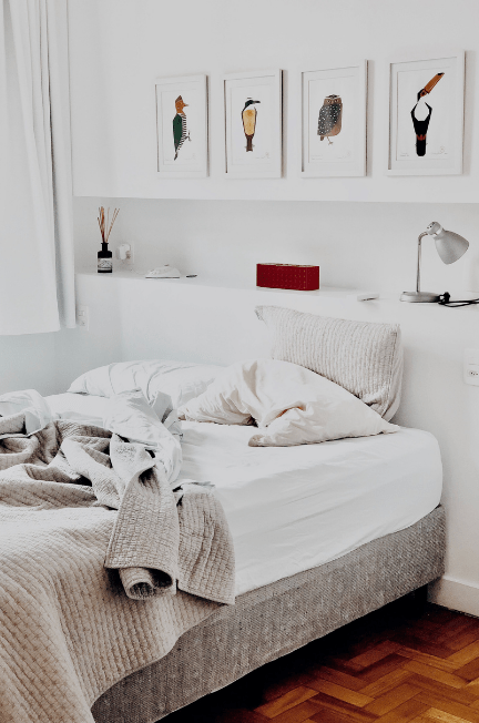 A messy white and grey bed
