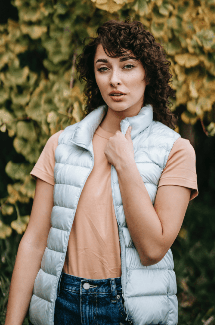 Woman wearing a silver puffer vest over an orange tee.