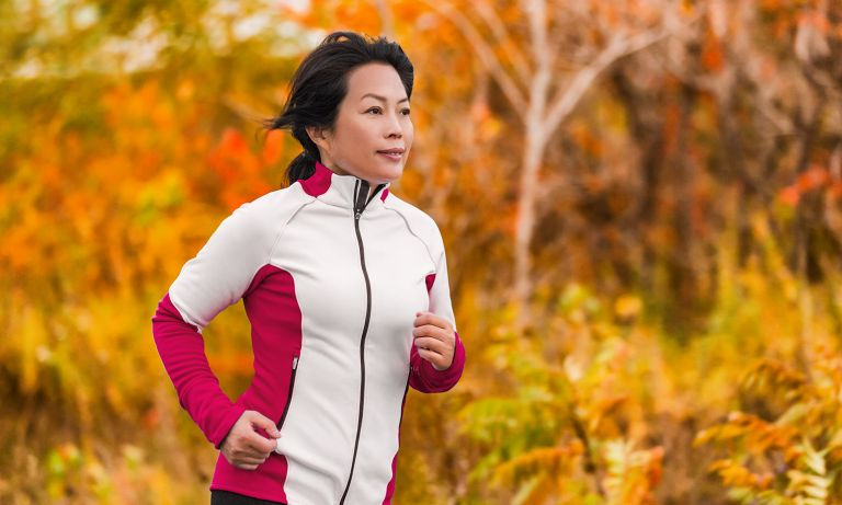 Woman in fleece jacket jogs with colorful autumn leaves in background