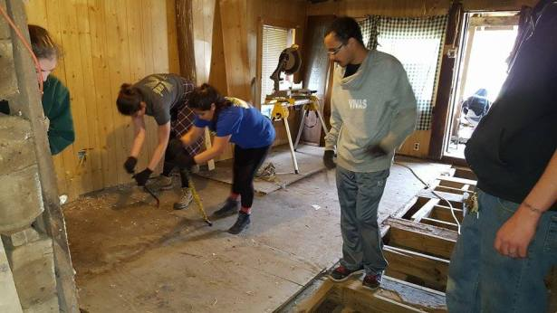 University of Richmond students tearing out old floor at the old cabin at Berwind Lake.