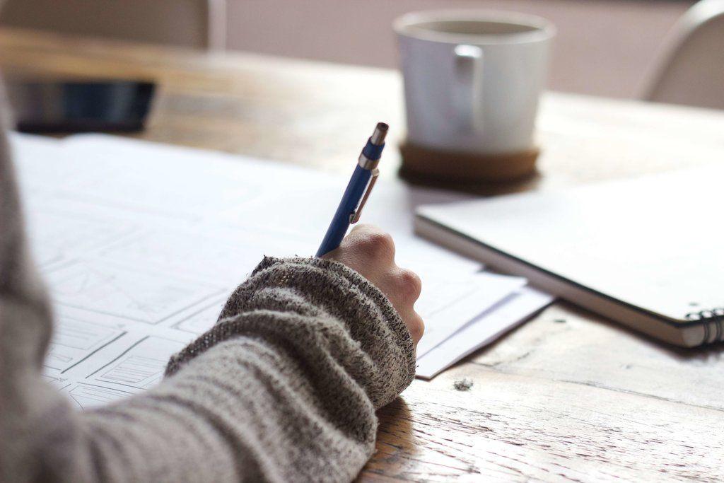 étudiant-concentré-qui-travaille-sur son-bureau-avec-efficacité