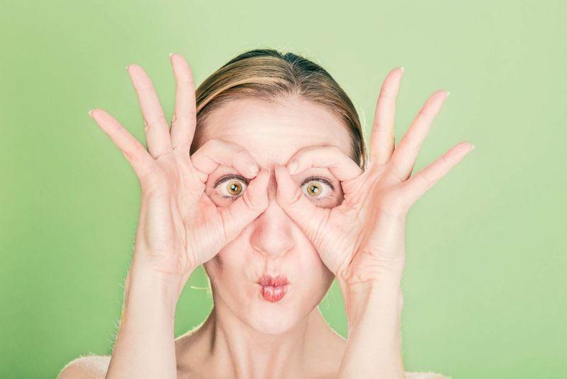 femme qui entoure ses yeux avec ses pouces et index