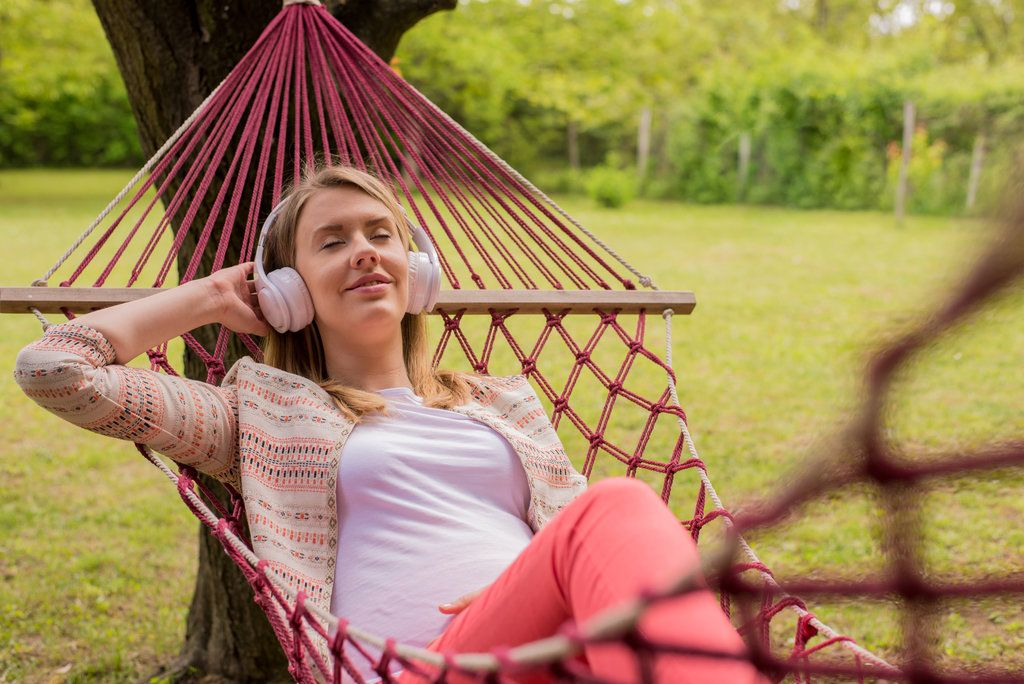 Close-up-portrait-of-woman-lying-down-on-hammock-listening-to-mu