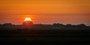 De zon gaat onder met een lach,...