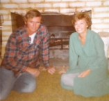 Aunt Carole and Uncle Chuck in front of the fire at the lake.