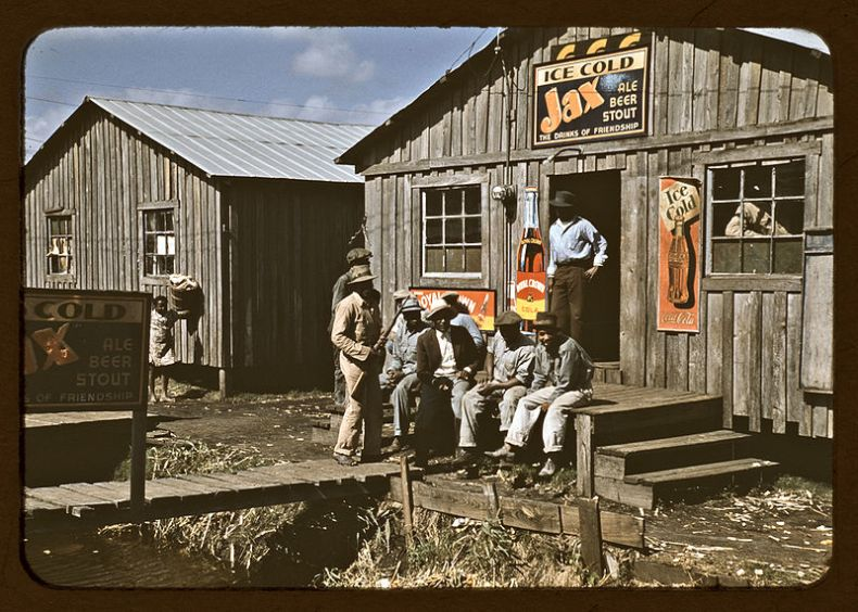 "Migratory laborers outside of a ""juke joint"" during a slack season, Belle Glade, Florida. Photographed by Marion Post Wolcott for the U.S. Farm Security Administration in 1944."
