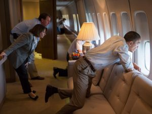 Barack obama looks ou through the window of the Air Force One from a Sofa