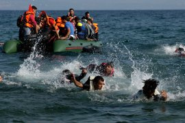 migrants in the water and boat crossing into greece