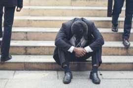 Man in Suit sitting on steps head down dejectedly