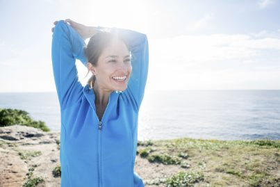 Happy young woman stretching her arms outdoors while enjoying the scenery