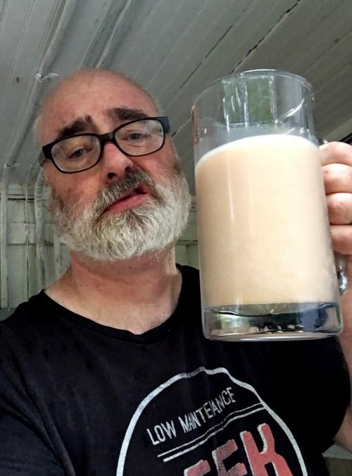 man holding mug of milky, light-brown liquid