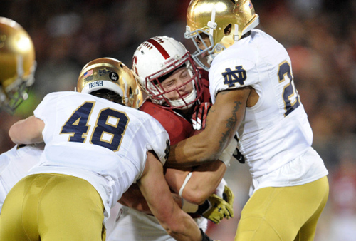 Stanford Cardinal running back Christian McCaffrey (5) is brought down by Notre Dame Fighting Irish linebacker Greer Martini (48) and safety Elijah Shumate (22) during the first half at Stanford Stadium.