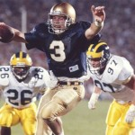 Notre Dame quarterback Rick Mirer scores a touchdown against the defense of Michigan's David Key (26) and Chris Hutchinson (97) at Notre Dame Stadium on Sept. 15, 1990. (Getty Images / John Biever)