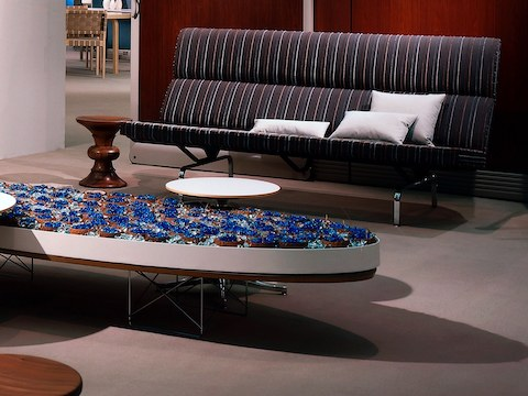 eames sofa compact sofabed factory lounge seating herman miller an with a striped fabric next to walnut stool in