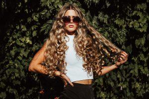 Dauerwelle Eine hbsche junge Frau mit Sonnenbrille und groen Locken