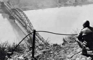 Ein GI blickt von der Erpeler Ley auf die eroberte Brücke (März 1945).