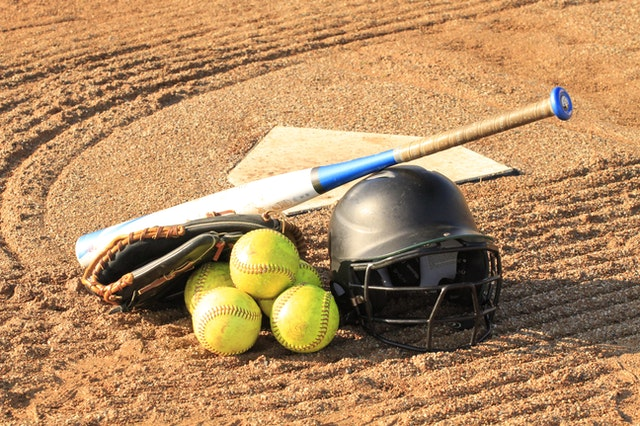 Baseball gear on the ground, symbolizing cleaning and storing sports gear, and tips to help your equipment last longer