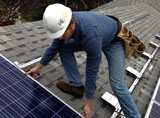 Eric Hoffman installing a solar panel on a home in Austin TX